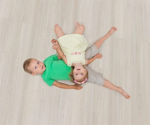 ash wood fusion cork floor kids lying on the warm floor playing at home